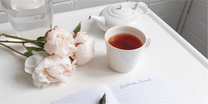 photo of gratitude journal, a cup of tea, and peonies