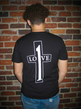 Load image into Gallery viewer, We love Him because He first loved us Black T-shirt