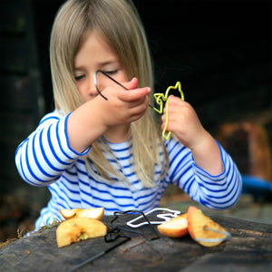 Girl putting apple bits onto a wire Bird Feeder