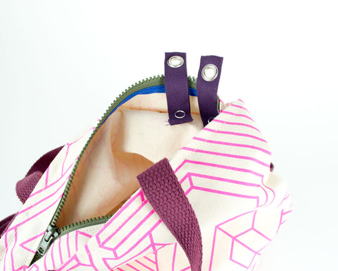 Detail of Backpack with adjustable straps and handles and zipper closure showing grommet snap system