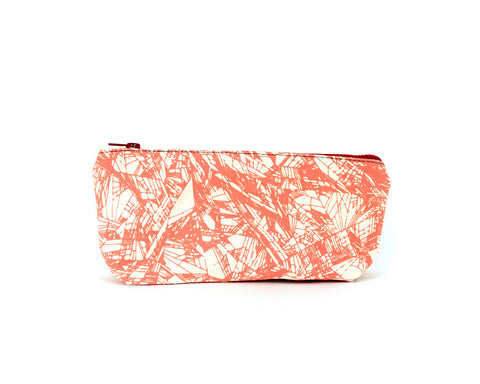 Knitting notions and pencil case with coral-colored abstract pattern.