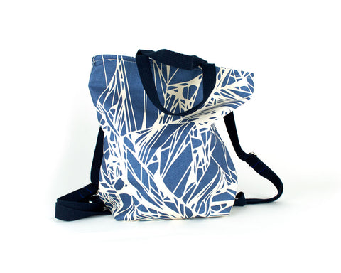 Backpack with adjustable straps and handles and zipper closure. Metallic blue geometric print.