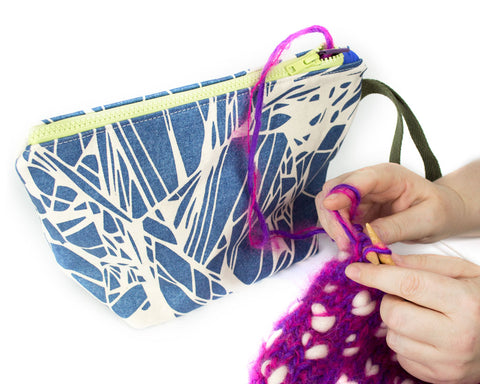 Woman using the small knitting project bag with interchangeable grommet and snap system.
