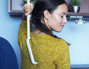 a smiling lady using the best folding back scratcher on her back