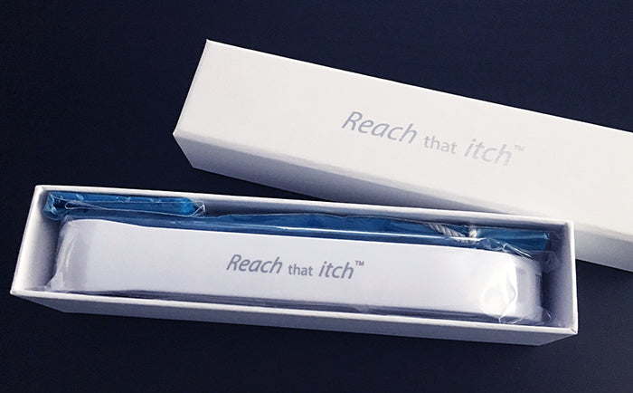 picture showing the Reach that itch back scratcher and the included velvet pouch in the gift box. The world's best back scratcher Reach that itch.