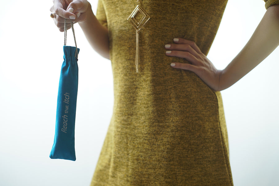 picture of a lady holding the world's best folding back scratcher (Reach that itch) in the included blue velvet travel pouch.
