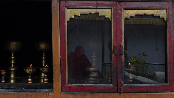 Lamps lit at the entrance to a monastery, while a monk is reflected in its glass