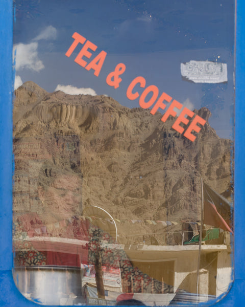 A lady serving aloo parathas and chai, with the majestic mountains reflected on her window