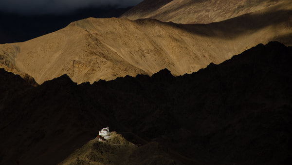 The sun shines it's spotlight on a monastery while the mountains play hide & seek.