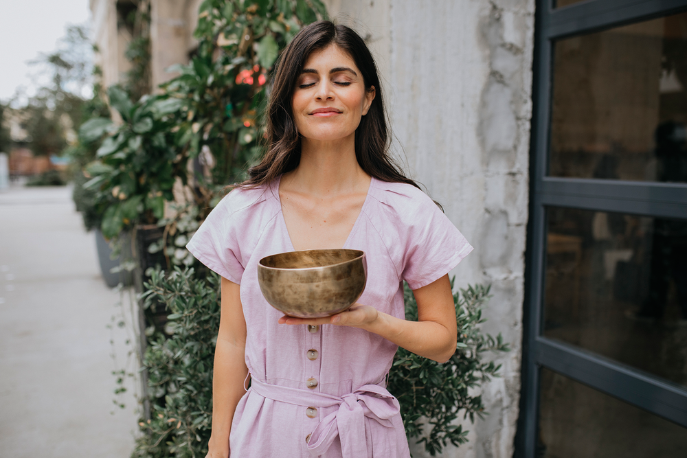 Ana Lilia standing in outside holding a brass bowl in her left hand and closing her eyes.