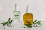 Bloomi Massage Oil and Bloomi Arousal Oil sitting on a white counter top in front of a white brick wall with decorative leaves on opposite ends.