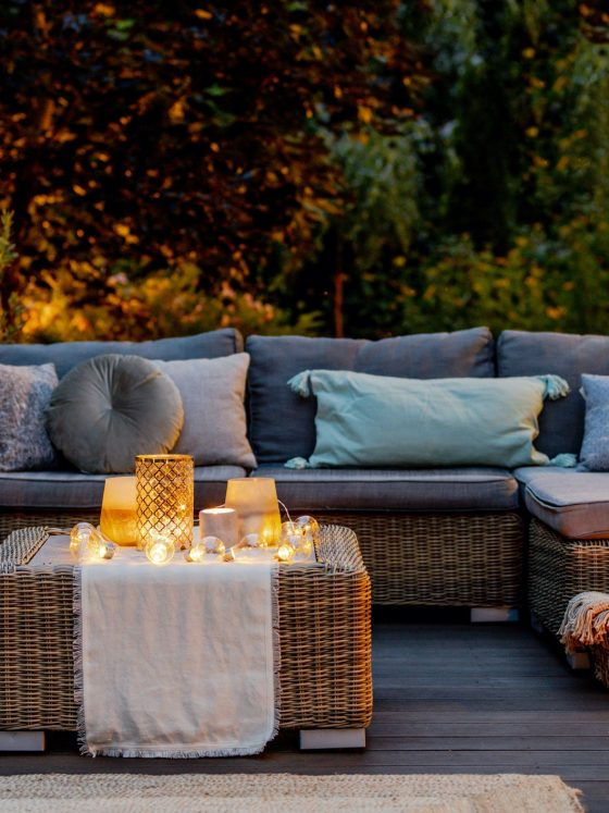 Candle-lit patio area with wicker outdoor seating and navy blue cusions for an intimate at home date night.