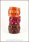 Handmade Leather Adjustable Claspless Slotted Wrist Cuff Bracelet, 2 inches wide, red brown and tan colors. By Erin Metcalf of Eirewolf Creations.