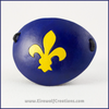 A handmade leather eye patch with a carved Fleur de Lis symbol, bright yellow on a dark blue background. By Erin Metcalf of Eirewolf Creations.