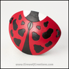 A cute handmade leather Ladybug eye patch, carved and painted red, black, and white. By Erin Metcalf of Eirewolf Creations.