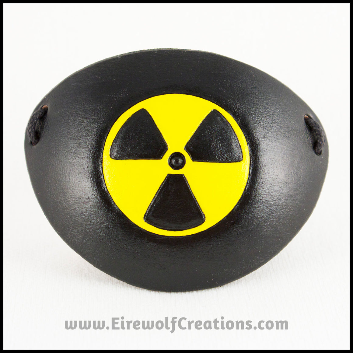 A handmade leather eye patch with a carved and painted radiation hazard symbol in black and yellow, for a masquerade costume or pirate cosplay. By Erin Metcalf of Eirewolf Creations.