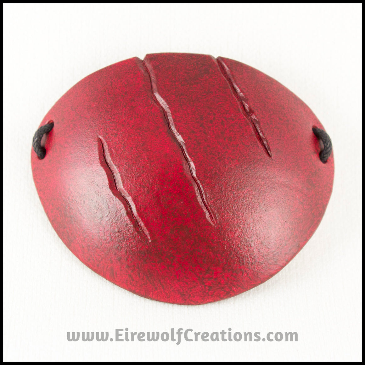 A handmade leather eye patch with three jagged scars carved diagonally, dyed and painted a mottled red reminiscent of blood, for a masquerade costume or assassin or pirate cosplay. By Erin Metcalf of Eirewolf Creations.