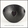 A handmade leather eye patch with a heart cut out, subtly iridescent black, backed with transparent black fabric to allow some visibility, for a masquerade costume or pirate cosplay. By Erin Metcalf of Eirewolf Creations.