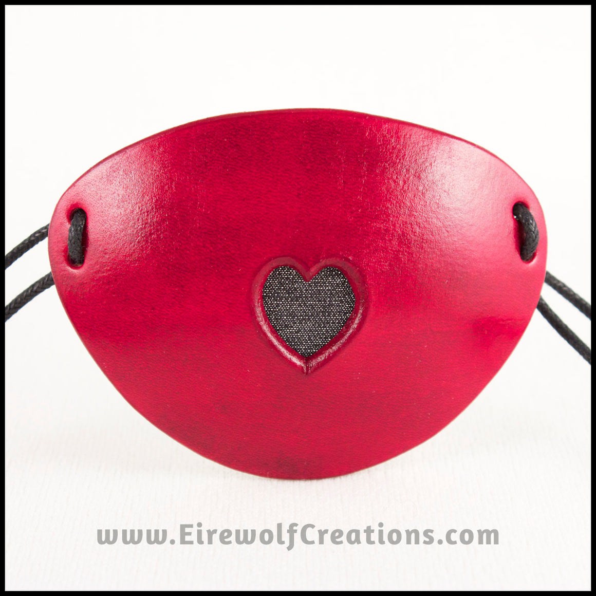 A handmade leather dyed red eye patch with a heart cut out, backed with transparent black fabric to allow some visibility, for a masquerade costume or pirate cosplay. By Erin Metcalf of Eirewolf Creations.