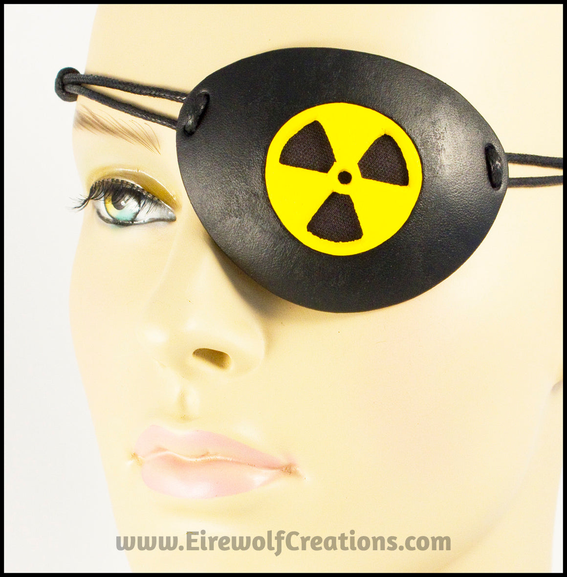A handmade leather masquerade costume eye patch with a radiation hazard symbol cut out of the leather, painted black and bright yellow and backed with transparent black fabric to allow some visibility. By Erin Metcalf of Eirewolf Creations.
