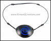 A thin spiral carved and painted cobalt blue, white, or dark red onto a handmade black leather eye patch, for a masquerade costume or pirate cosplay. By Erin Metcalf of Eirewolf Creations.