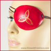 A handmade leather eye patch with a triquetra, or Celtic trinity knot, carved and painted copper on a dyed red background, for a masquerade costume or pirate cosplay. By Erin Metcalf of Eirewolf Creations.