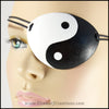 A handmade leather eye patch with a bold black and white yin yang symbol carved and painted over the whole eye patch, for a masquerade costume or pirate cosplay. By Erin Metcalf of Eirewolf Creations.