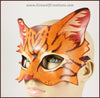 A handmade leather tabby cat mask for a masquerade costume, light brown with handpainted dark brown stripes and a dark pink nose and inner ears. By Erin Metcalf of Eirewolf Creations.
