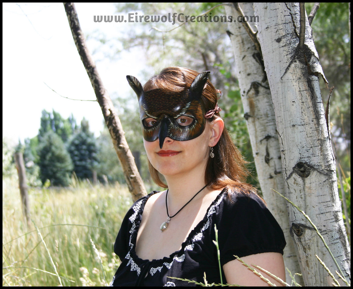 A Great Horned Owl handmade leather masquerade costume mask, dyed dark brown and carved and painted with feather details. By Erin Metcalf of Eirewolf Creations.