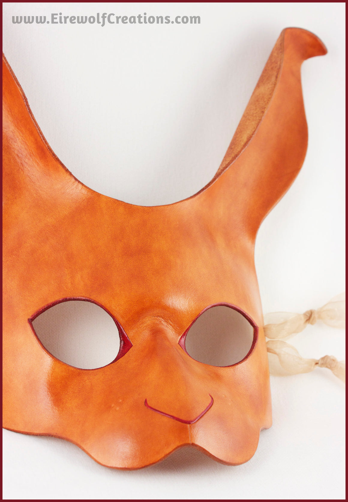 A handmade leather rabbit mask for a masquerade costume, dyed light brown with subtle red details painted around the eyes and nose. By Erin Metcalf of Eirewolf Creations.