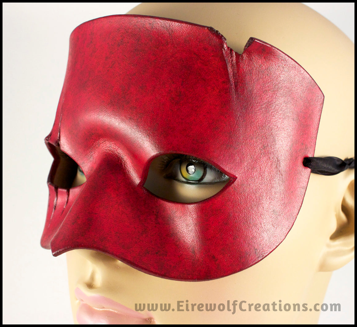 A handmade leather mask with 3 scars slashing across one eye, dyed and painted a mottled red reminiscent of blood. By Erin Metcalf of Eirewolf Creations.