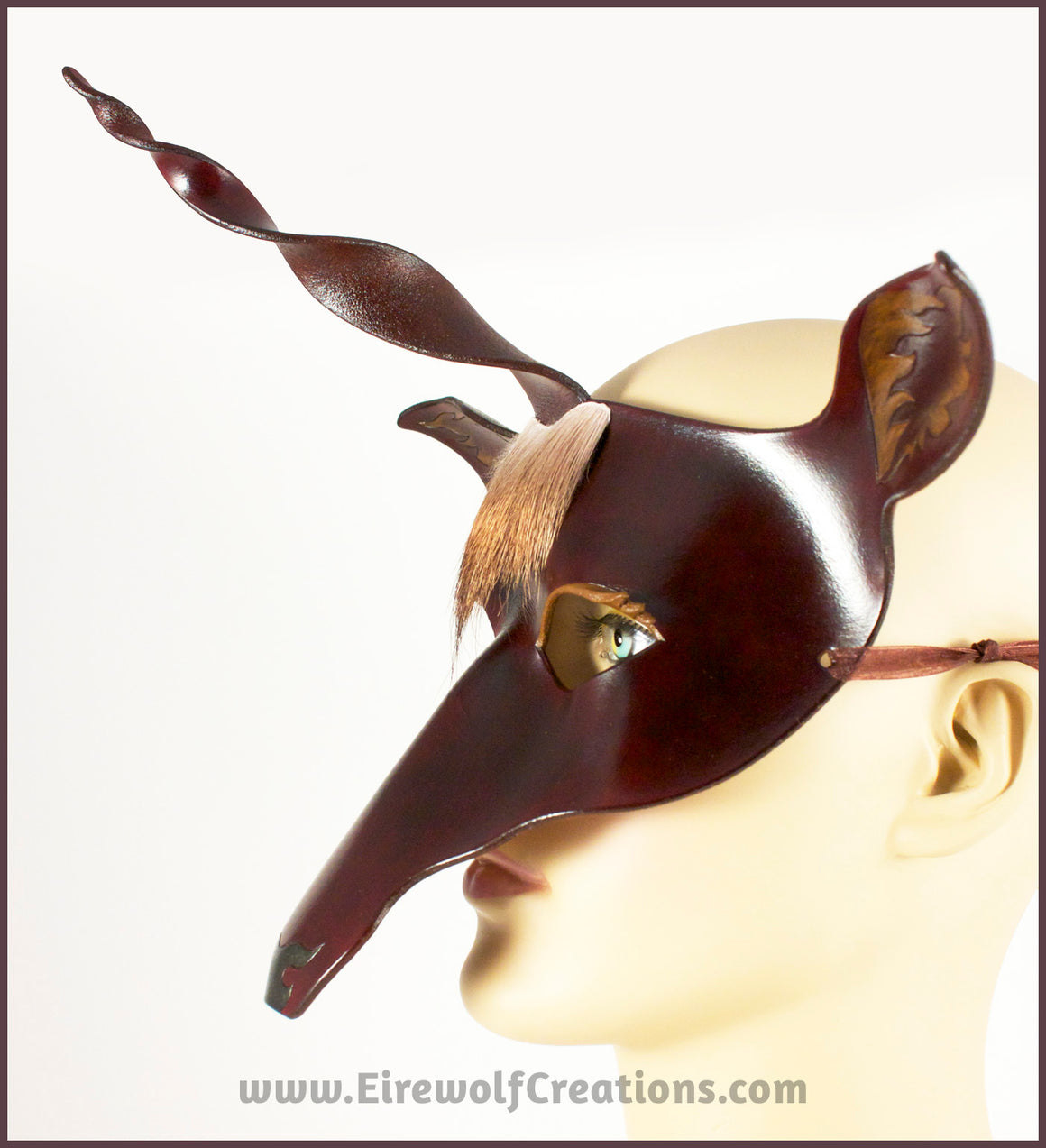 The Dark Forest Unicorn is a dark brown handmade leather masquerade mask of a deerlike unicorn with real deer hair as a forelock. By Erin Metcalf of Eirewolf Creations.