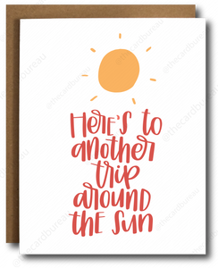 "high quality greeting card with image of yellow sun and red cursive text that reads ""Here's to another trip around the sun"""