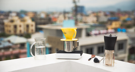A Pearl Scale on the ledge of a building with other coffee equipment.
