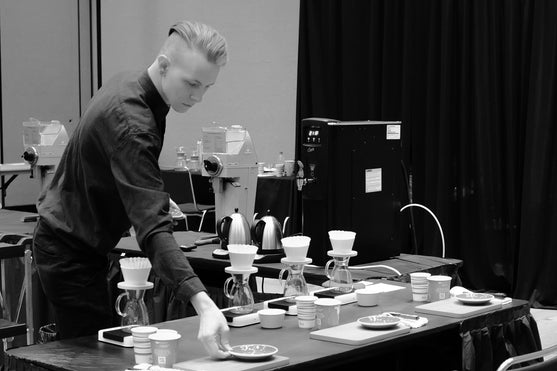 A barista competitor organising their set up.