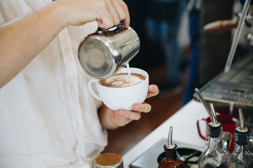 A close up photograph of a barista pouring an espresso based milk drink.