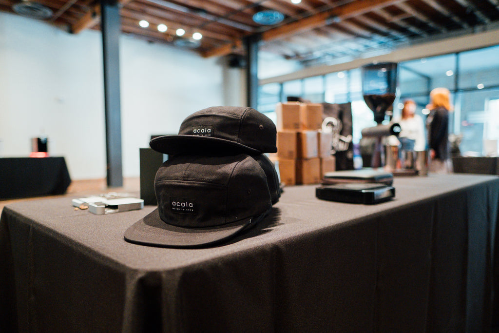 Several of the Acaia hats sitting on a table at a convention.
