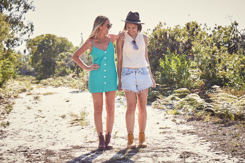 two girls walking in nature wearing merry people boots