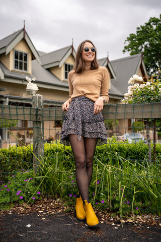 girl leaning against a fence wearing merry people mustard boots, mini skirt, jumper