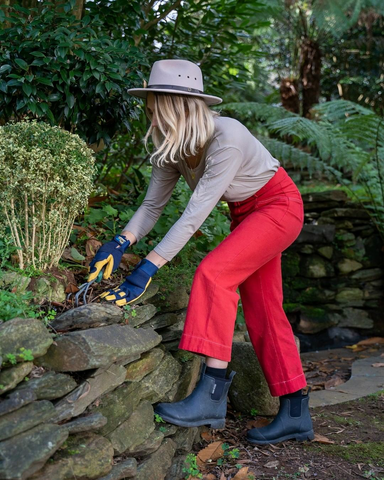woman in red pants, black merry people boots, gardening