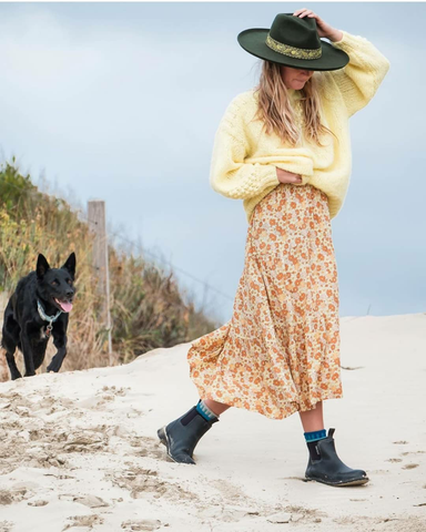 woman walking on the beach with her dog, wearing floral boho dress and merry people green gumboots