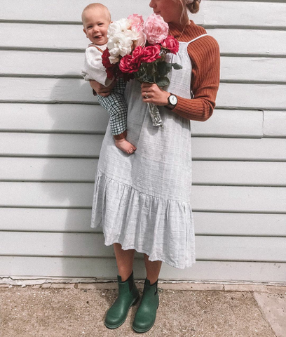 women wearing green merry people boots, wearing grey dress and jumper and holding flowers