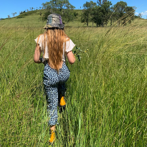 woman walking through tall grass wearing yellow boots