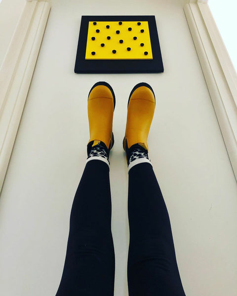 women wearing merry people yellow boots, legs leaning up against a wall