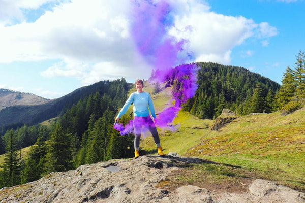 women on a mountain top colour bombing purple