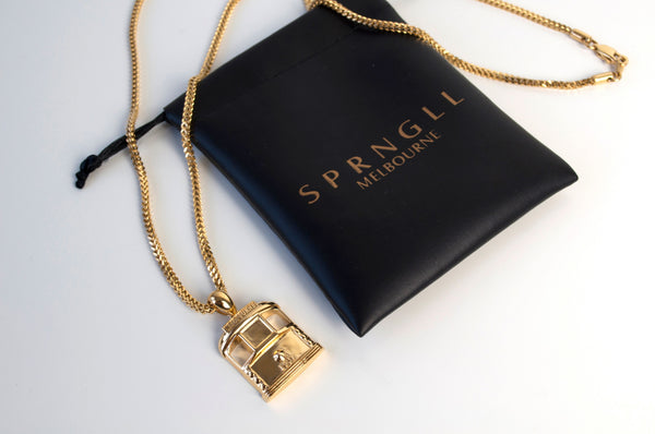 Gold Tram pendant and chain on black SPRNGLL gift bag