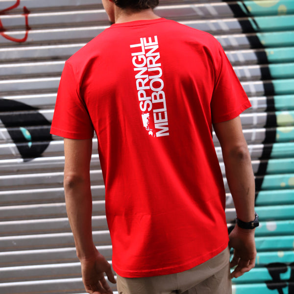 A man wearing a red t-shirt with bold white writing on it. Facing the other way in a laneway in Melbourne