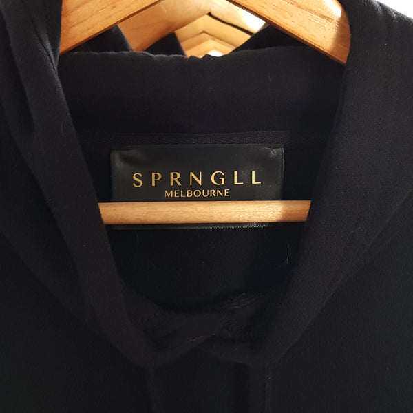 Black hoodie hanging on a clothes hanger close up of tag that says SPRNGLL Melbourne