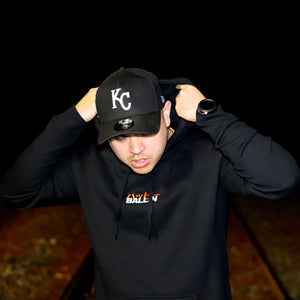 Man standing in a black hoodie with happy ballin embroidered on the chest and a black beanie on with black joggers