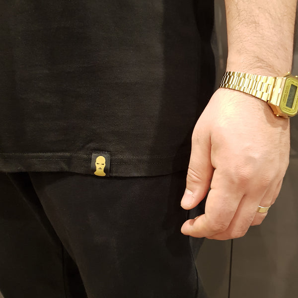 Men's Black Tee Shirt zoomed in on front label with balaclava on it and wearing a gold watch